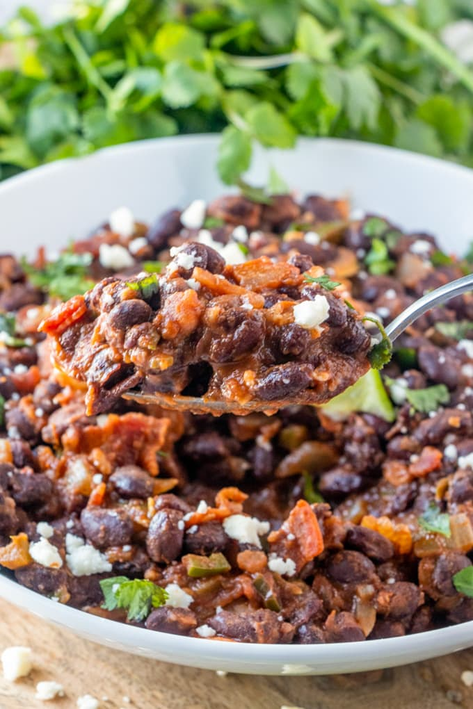 Black beans with salsa and bacon in a large dish with a spoon lifting up a serving.