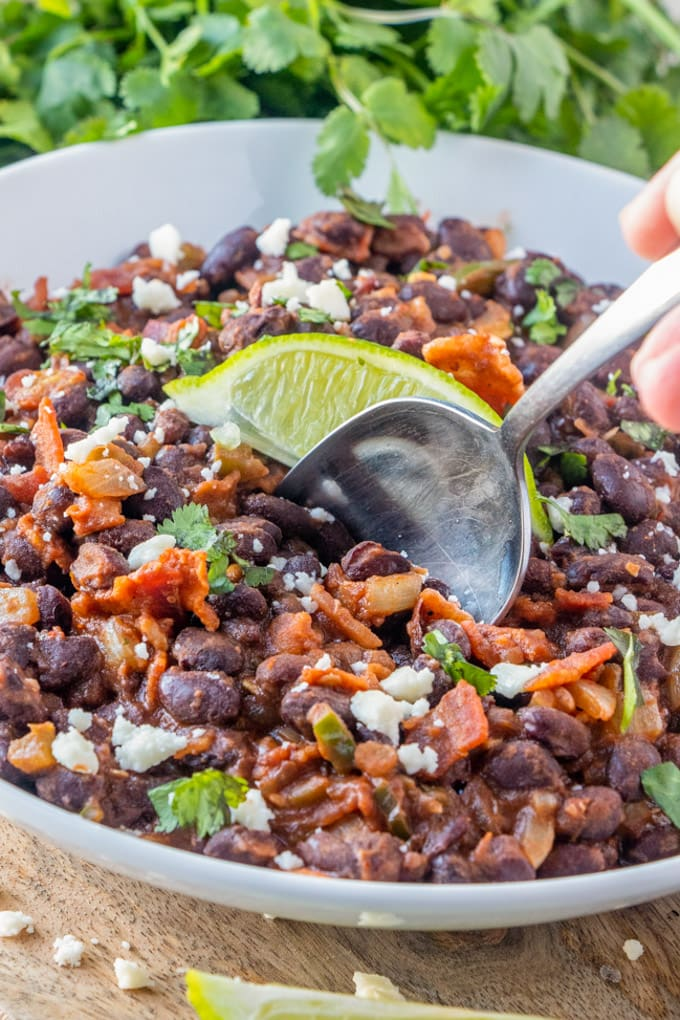 a large bowl of mexican black beans with a spoon and a lime slice.