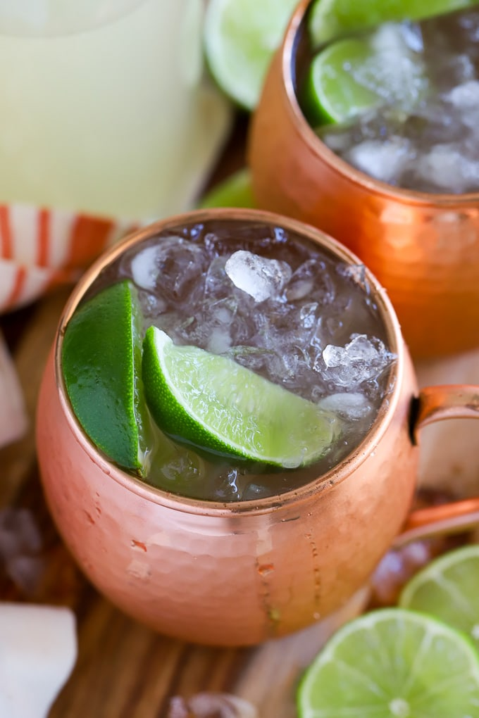 Moscow Mule in a copper mug garnished with lime two lime wedges.