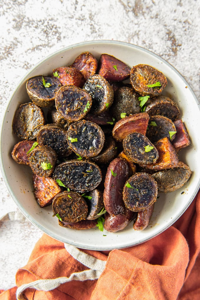 a white bowl full of roasted purple potatoes sitting next to an orange towel