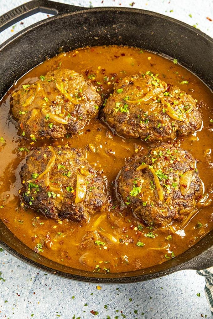 Salisbury Steaks simmering in a pan