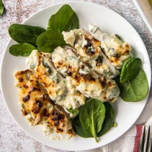 A plate of spinach artichoke chicken with spinach