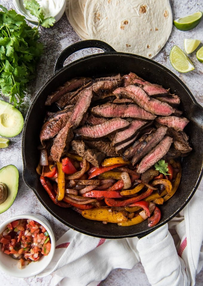 an overhead shot of sliced steak and peppers in a skillet, surrounded bu salsa, avocado and tortillas