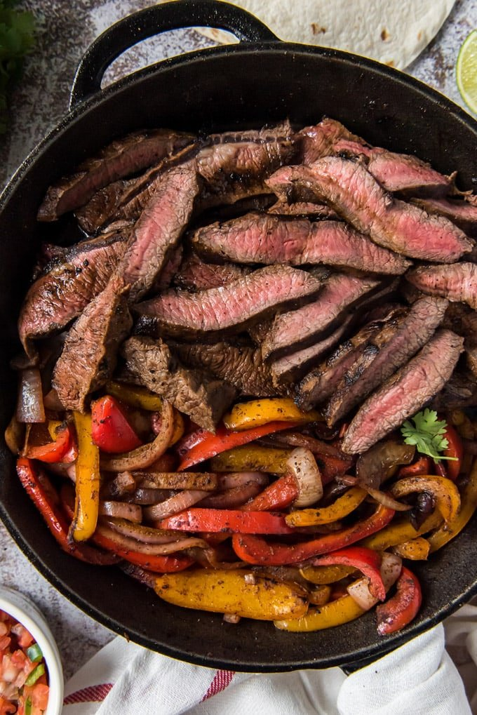 A cast iron skillet with sliced steak, bell peppers and onions.