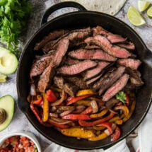 A cast iron skillet with Steak Fajitas