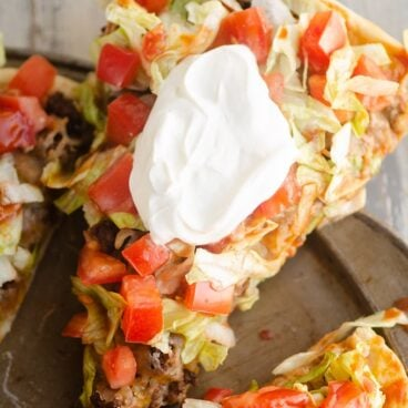 slice of taco pizza served with sour cream
