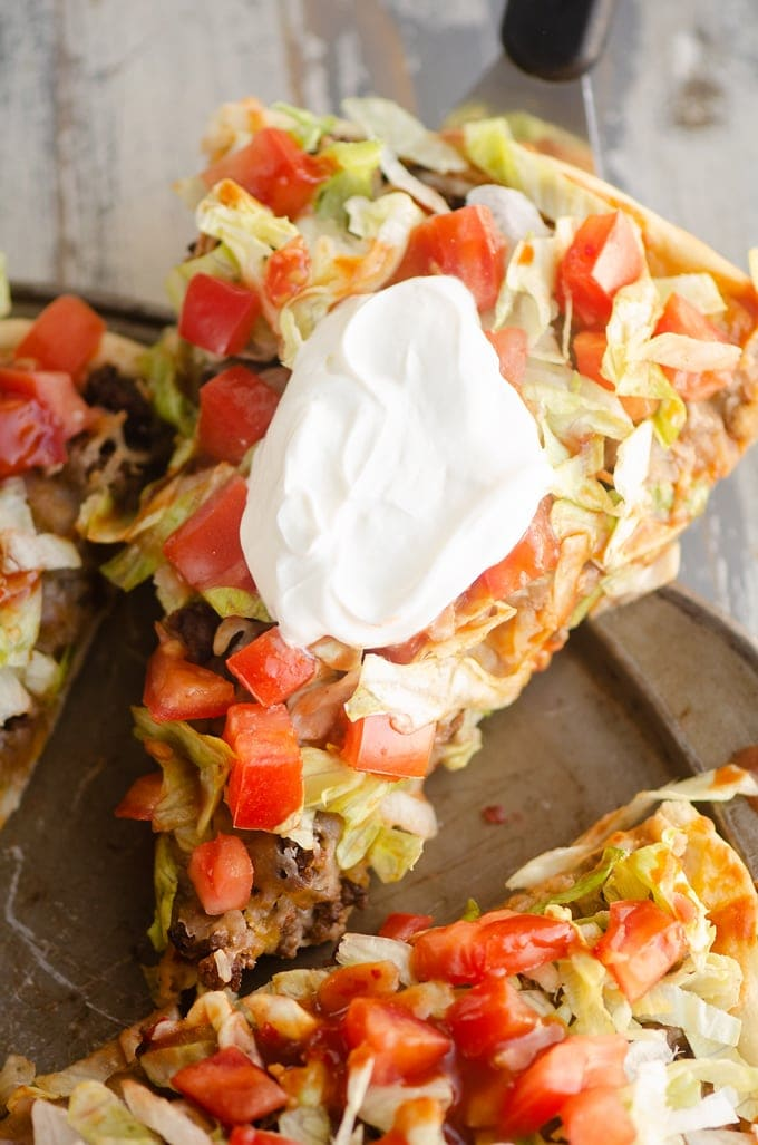 Slice of taco pizza with sour cream