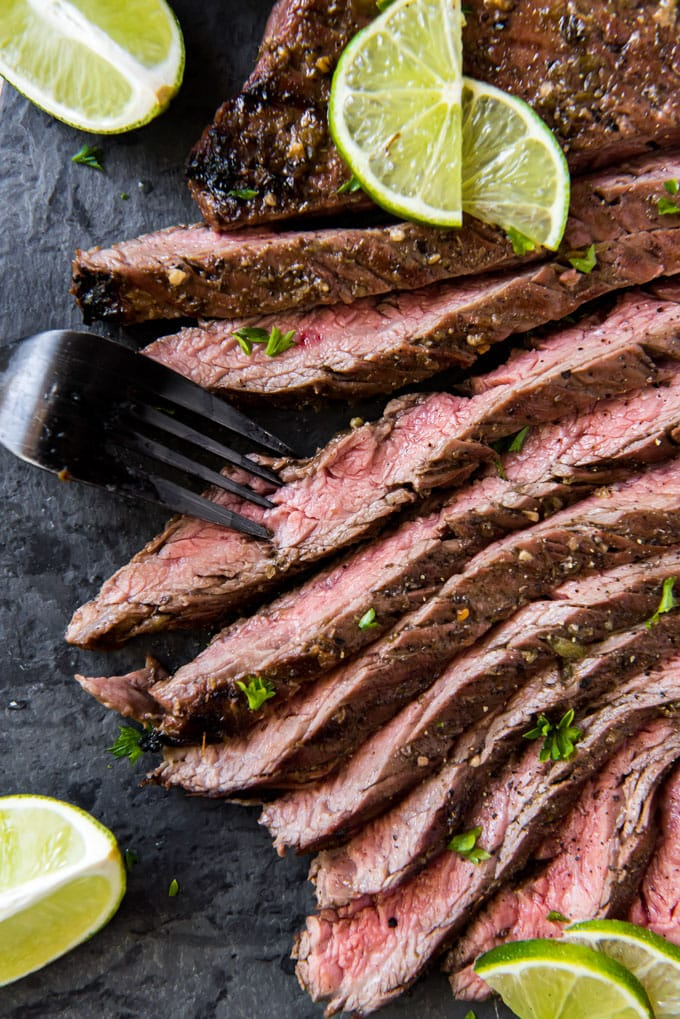 carne asada steak sliced on a black cutting board with a fork.