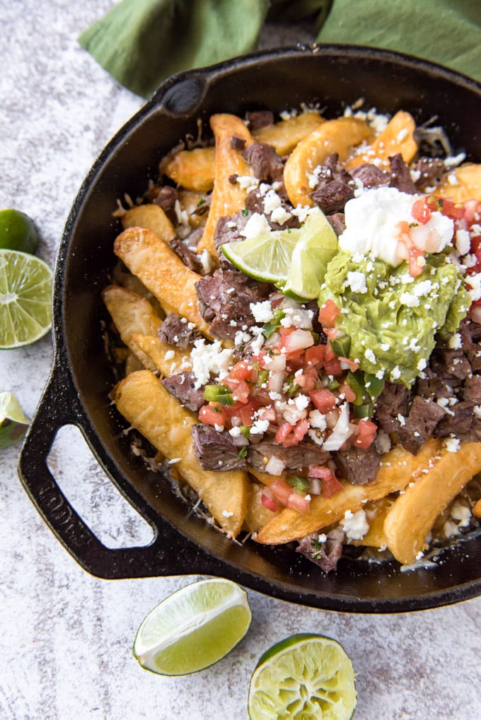 a large cast iron skillet with french fries, steak, guacamole and cheese