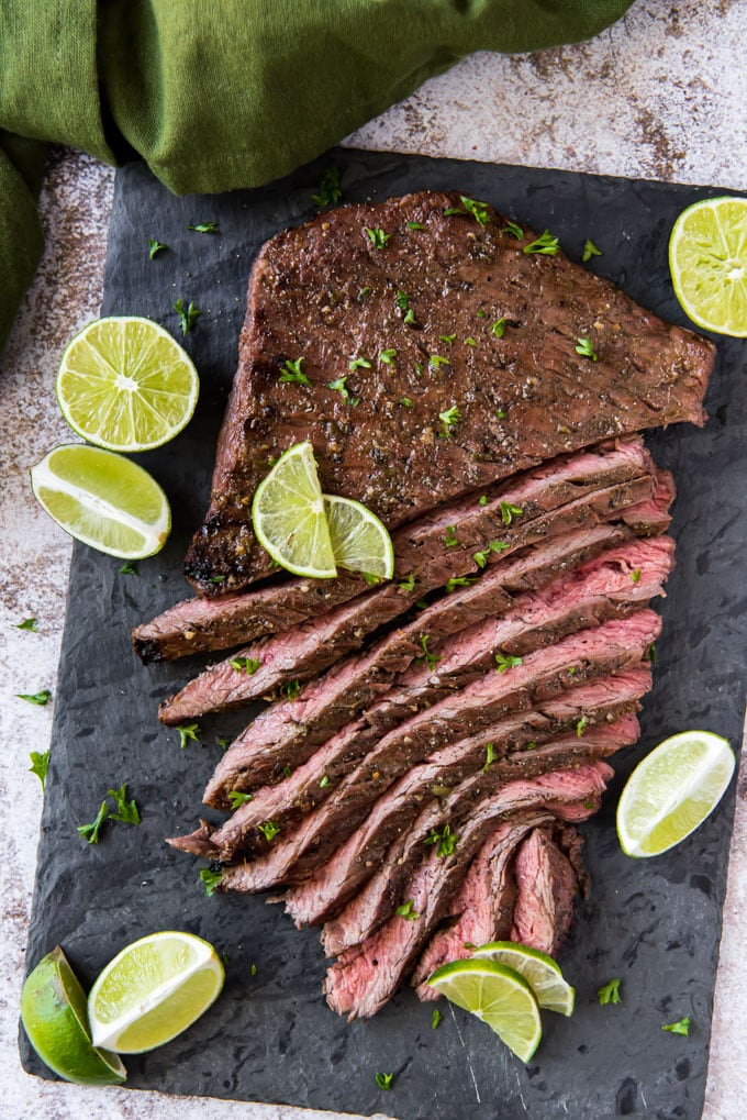 an overhead image of a large marinated and grilled flank steak, cut into strips and surrounded by sliced limes