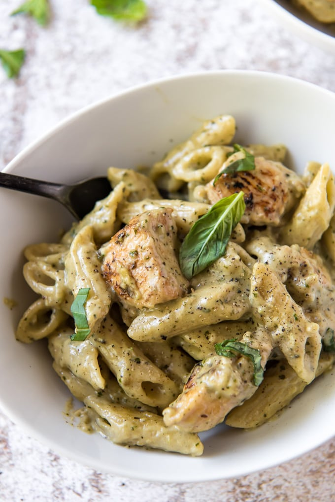 a white bowl with chicken pesto pasta in a creamy pesto sauce
