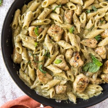 A skillet with pasta and chicken in a creamy pesto sauce