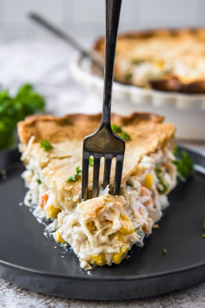 a slice of chicken pot pie with a fork in it.