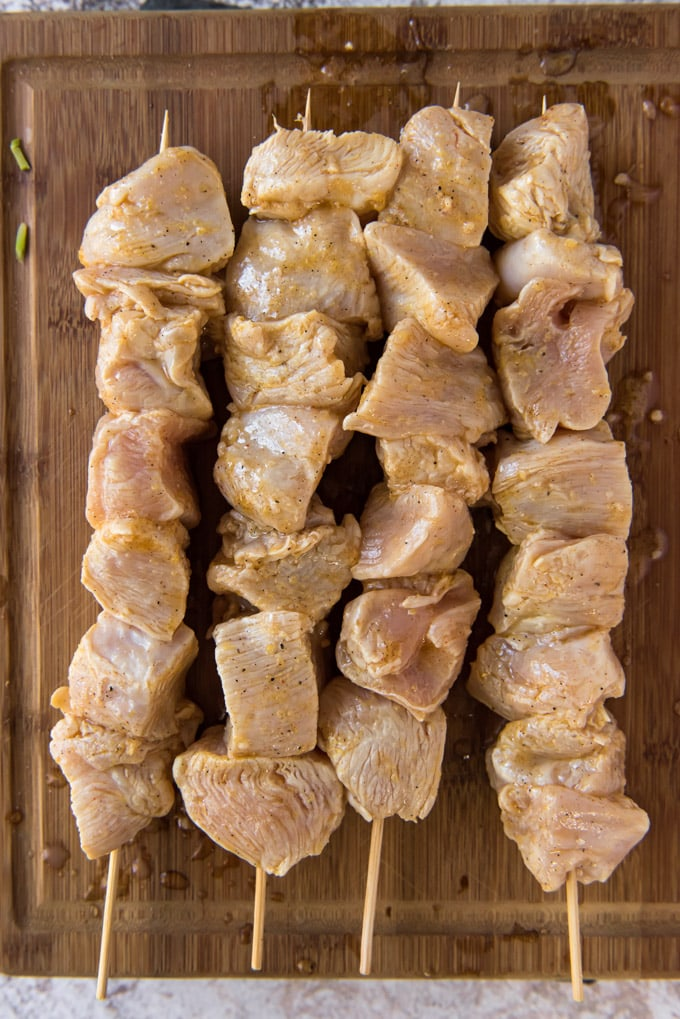 raw chicken breast chunks in marinade and threaded on wooden skewers.