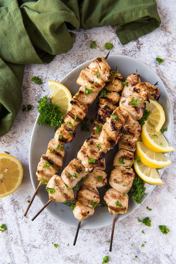 cut up chunks of chicken on skewers, grilled, with lemon on a plate