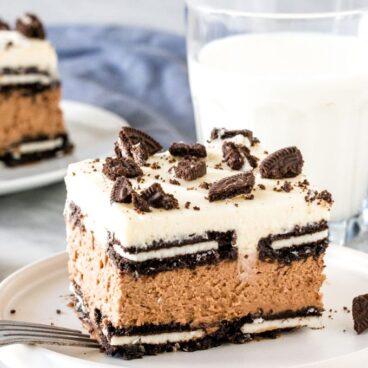 Slice of oreo icebox cake with glass of milk.