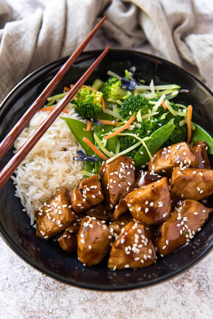 Close up overhead shot of a bowl with teriyaki chicken, vegetables and rice and chopsticks