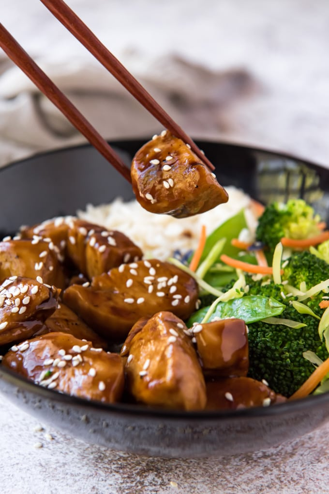 chopsticks holding a piece of teriyaki chicken over a bowl of rice and veggies