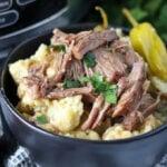 black bowl of mississippi pot roast on top of mashed potatoes