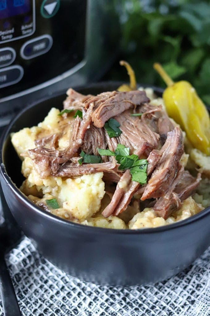 black bowl of mississippi pot roast on top of mashed potatoes