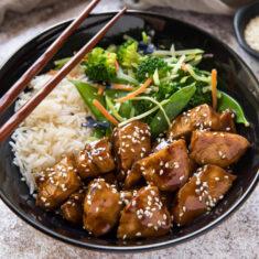 A bowl of teriyaki chicken, white rice, salad, and chopsticks.