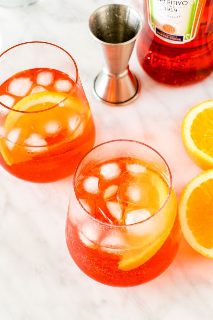 2 aperol spritz cocktails with ice and orange slices.