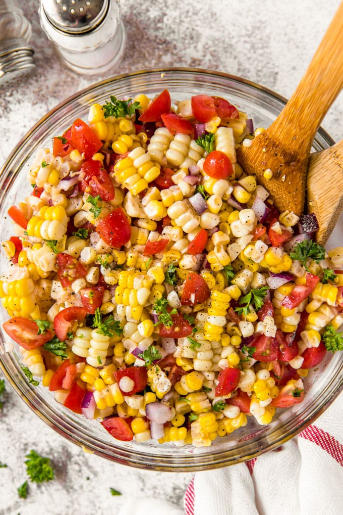 A bowl of corn salad with tomatoes, parsley and onions with two wood spoons sticking out.