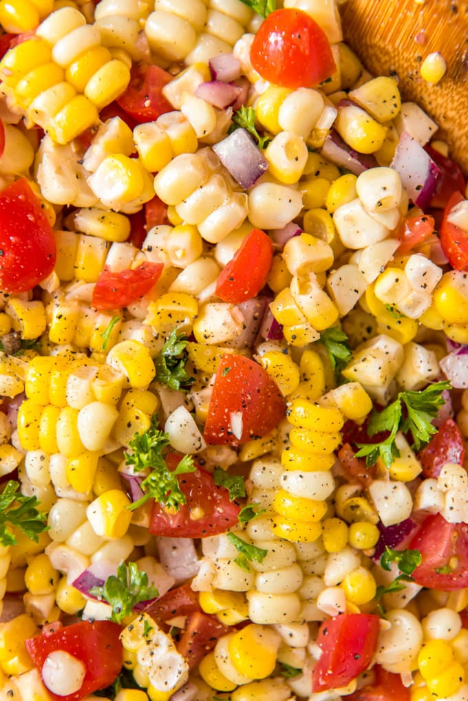 a close up of a corn salad with tomatoes and onions.