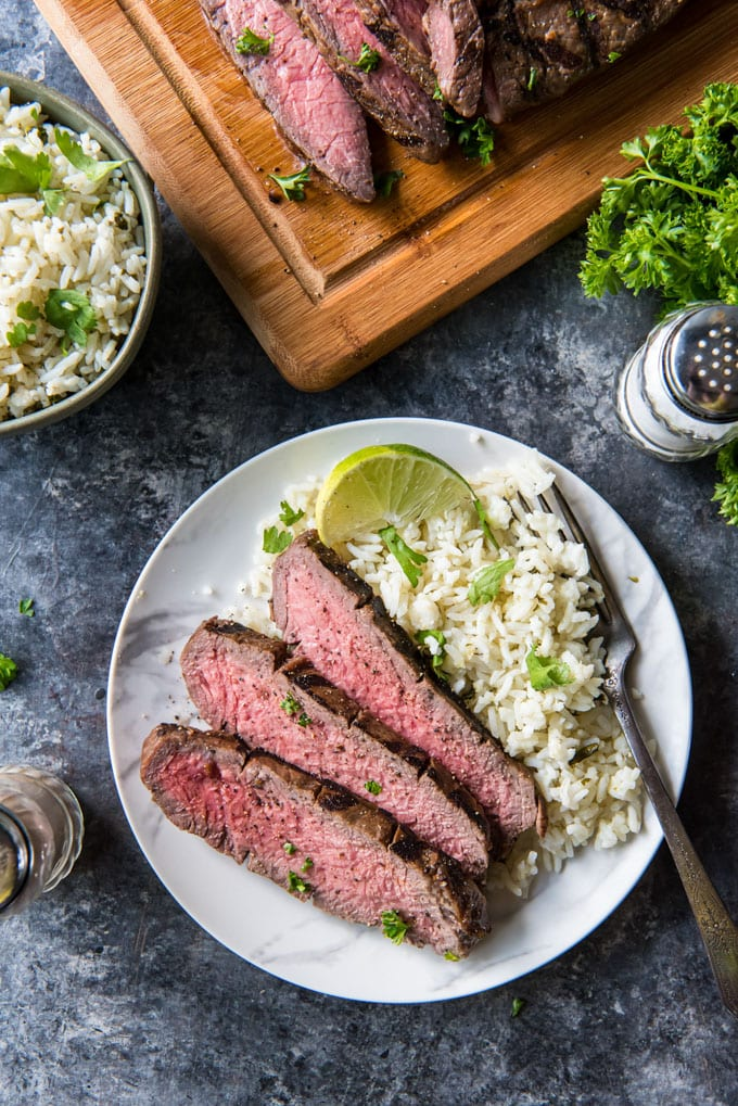 a small plate with sliced steak and rice on it.