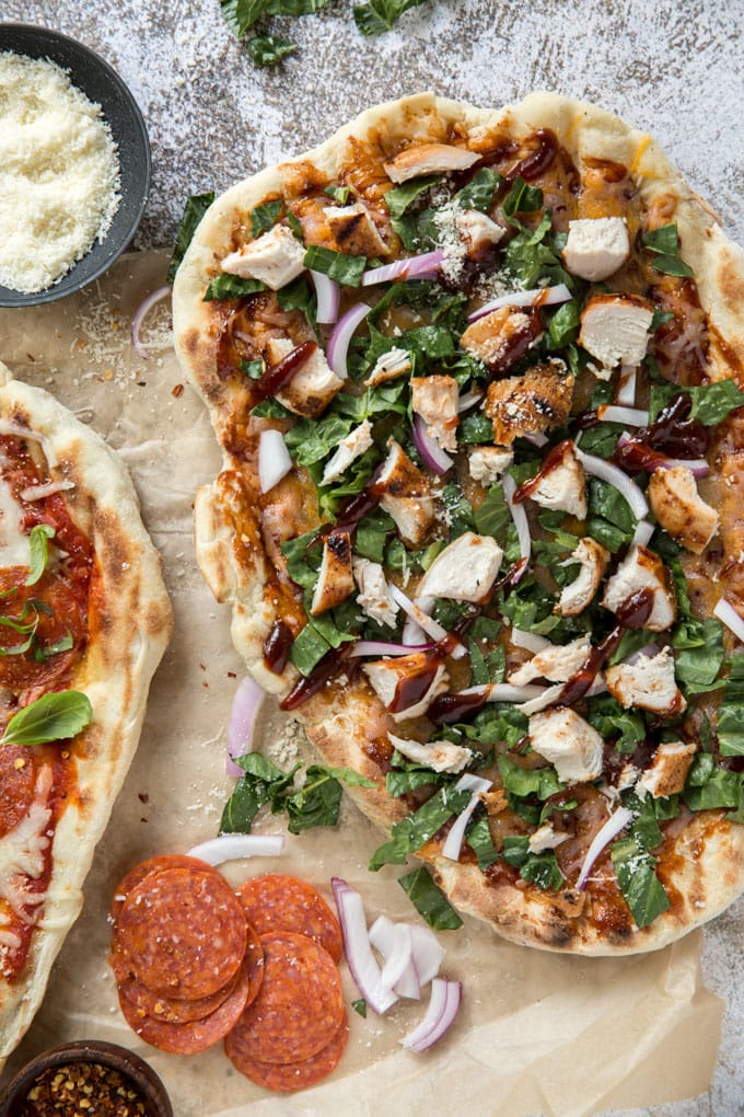 a grilled pizza crust with cheese, onions, chicken and basil. Sits on a whitewashed background