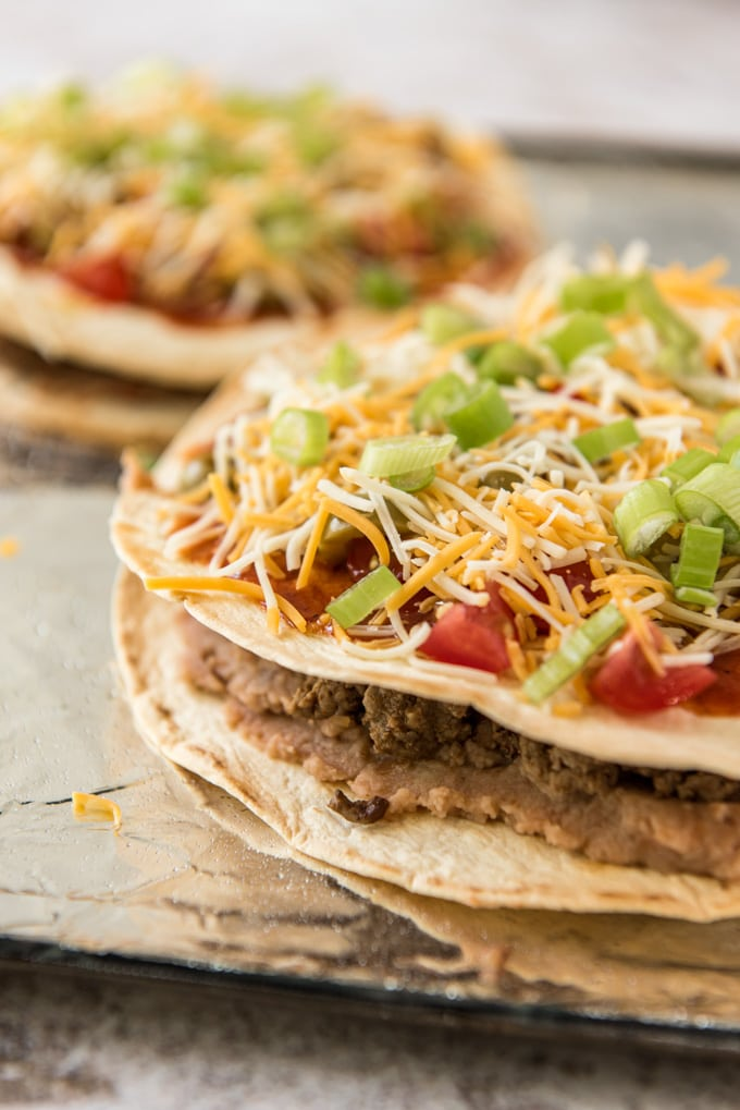 Crispy tortillas layered with beef and beans and topped with sauce, tomatoes and cheese