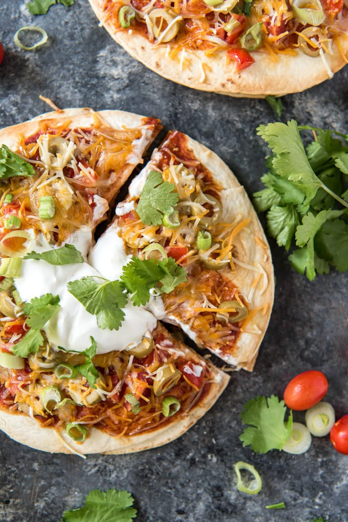 Mexican pizzas topped with cheese, sauce and sour cream