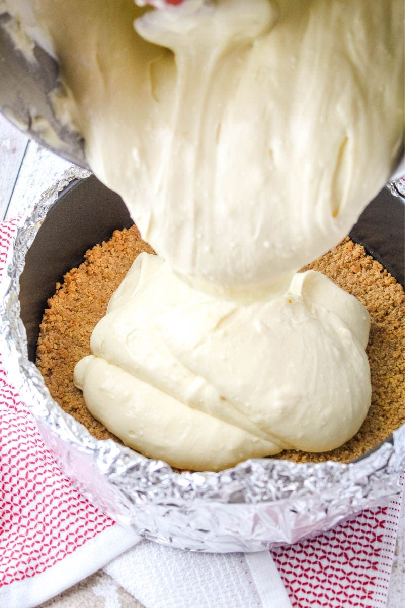 cheesecake batter being poured into a springform pan with a graham cracker crust