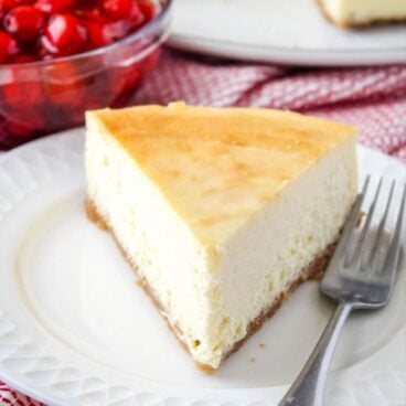 slice of new york cheesecake on a dessert plate with a fork