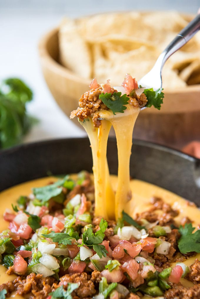 a fork lifting stringy yellow cheese from a pan of queso fundido