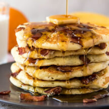 A plate of Bacon Pancakes topped with butter and syrup.