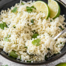 A plate of white rice with cilantro and lime