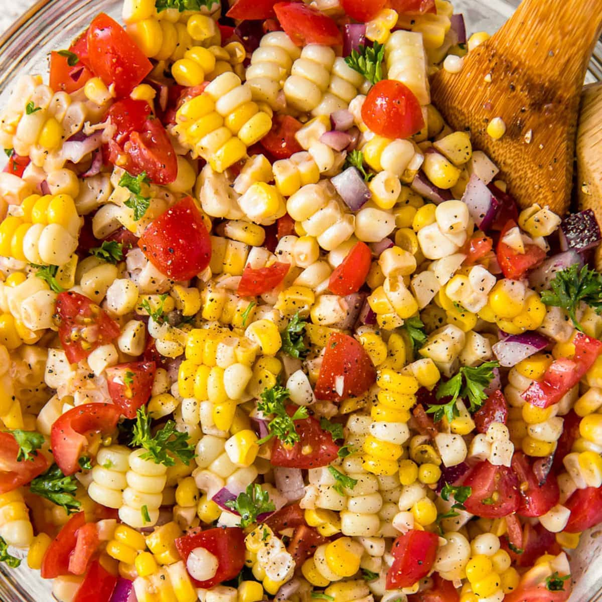 A dish full of corn salad with tomatoes