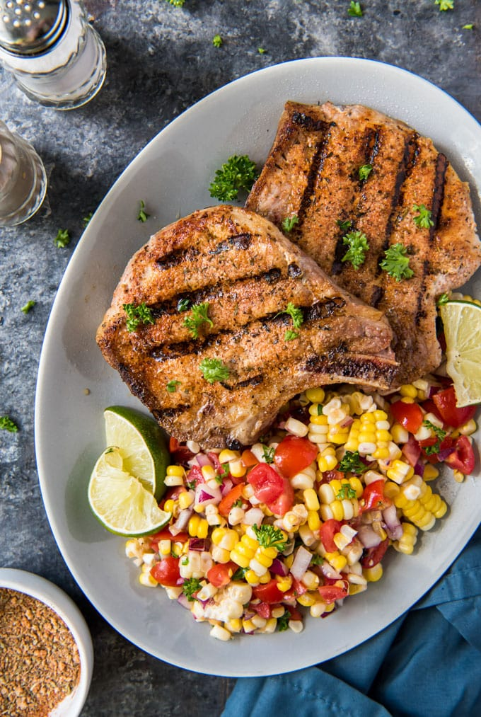 a large white plate with two grilled pork chops and corn salad on the side.