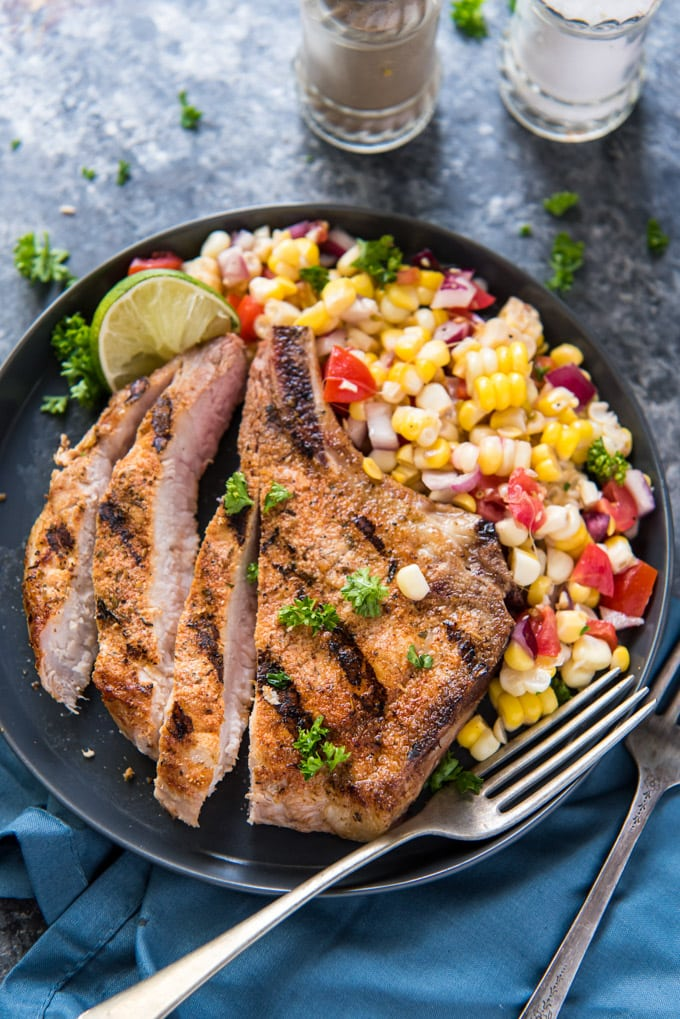 A grilled pork chop on a plate, sliced, with some corn salad on the side.