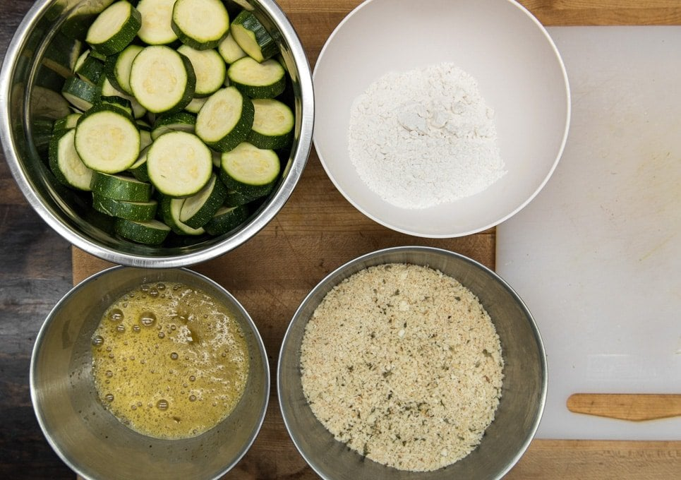 4 bowls with sliced zucchini, flour, whisk egg, and breadcrumbs.