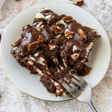 Slice of fudgy chocolate cake with marshmallows on a plate.
