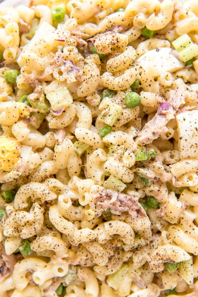 A close up image of tuna macaroni salad with peas, onions and macaroni.