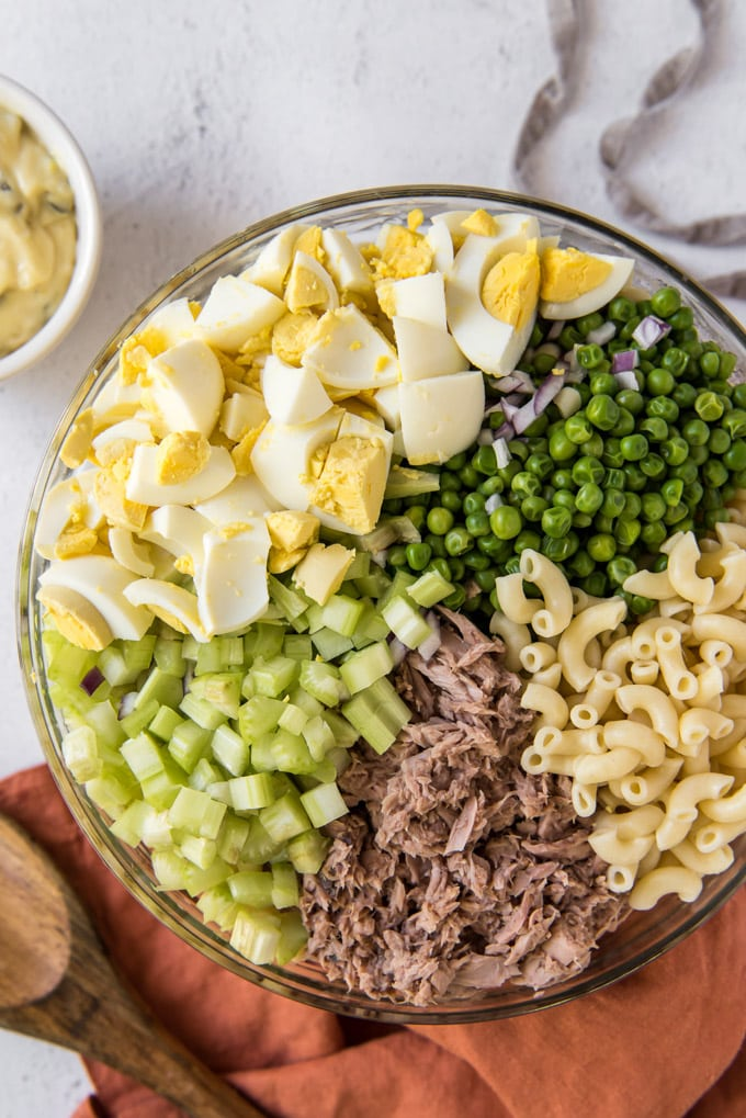 a large glass bowl with ingredients for tuna macaroni salad - chopped hard boiled eggs, peas, celery, tuna and macaroni.