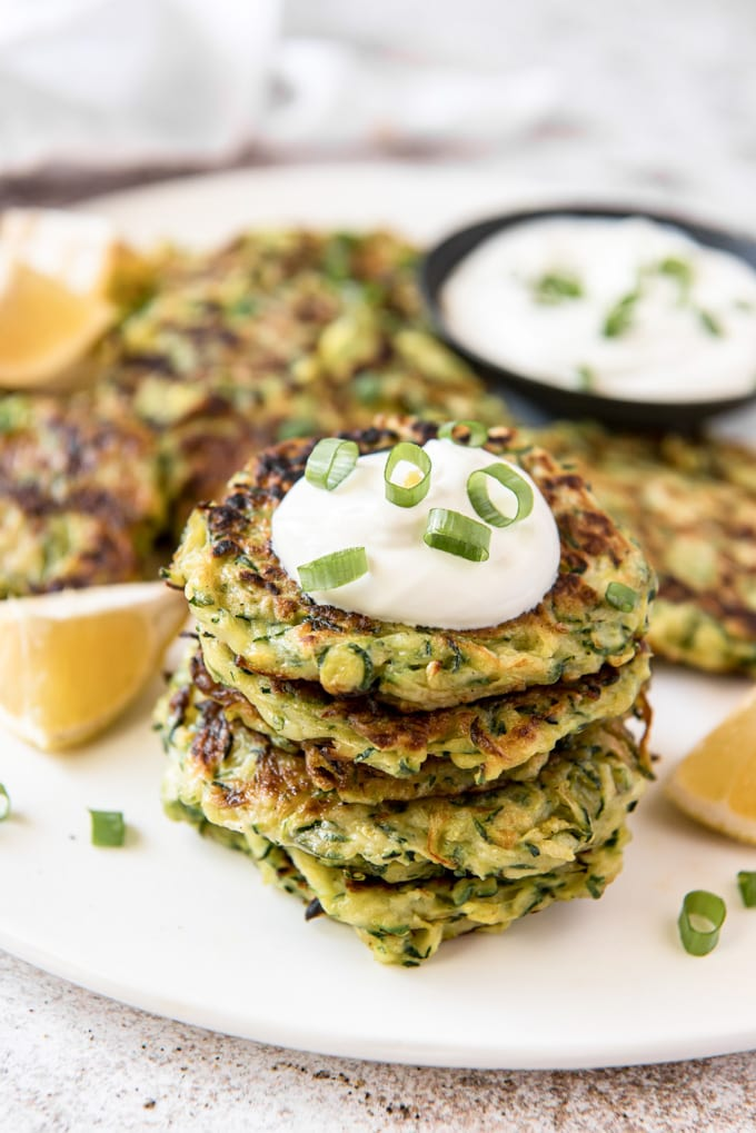 a stack of zucchini fritters topped with a dollop of sour cream and sliced green onions. More fritters, a dish of sour cream and lemon wedges in the background.