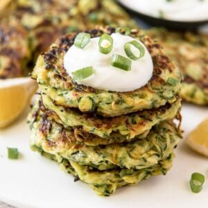 Stack of zucchini fritters with sour cream and green onions on top