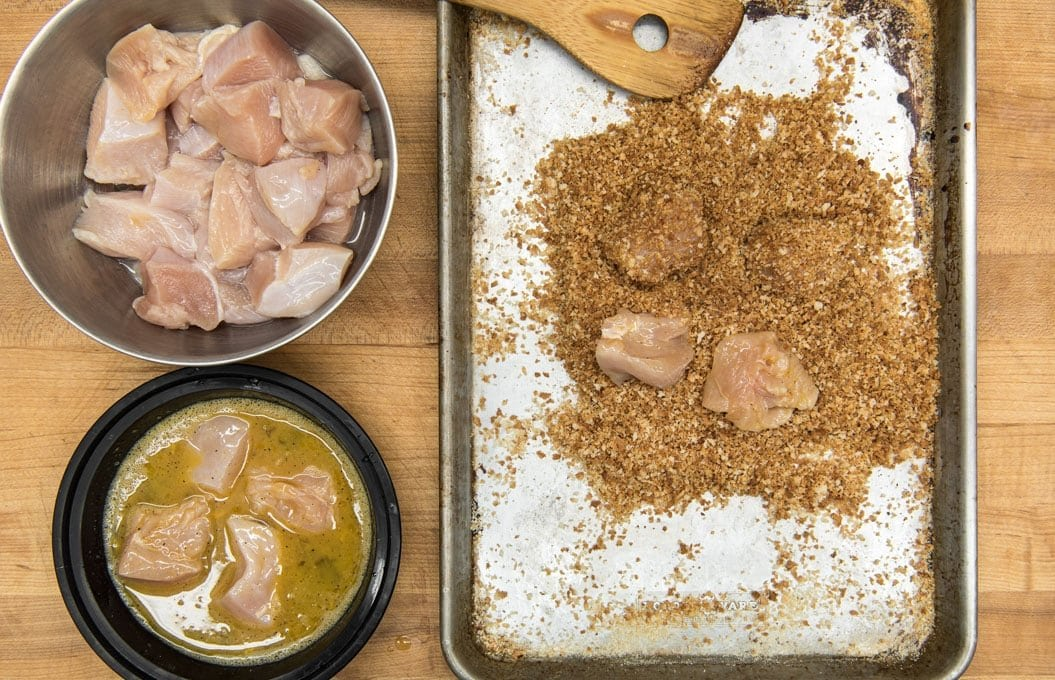 a wood cutting board background, a silver bowl with raw chicken nuggets, a black dish with whisked egg and 4 pieces of chicken and a silver baking sheet with a wood spoon, breadcrumbs and 3 pieces of raw chicken.