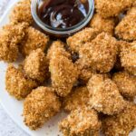 Breaded and baked chicken nuggets with small dish of barbecue sauce.