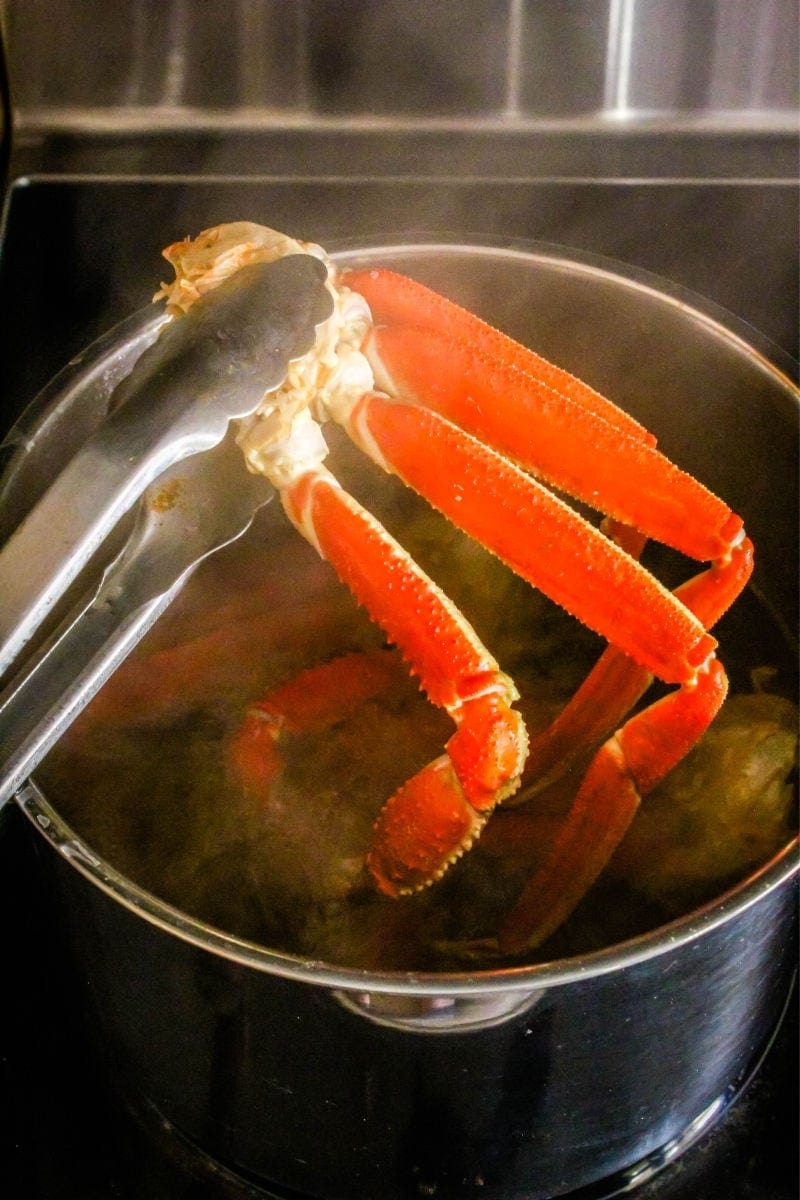 tongs lifting crab legs out of a pot of water