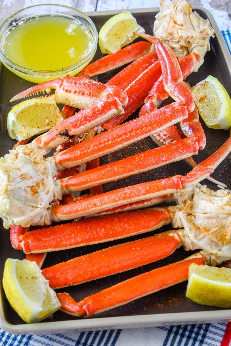 snow crab clusters on a plate with lemon wedges and melted butter